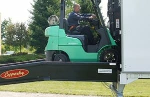 Copperloy® portable yard ramp level off image showing the forklift driving off the yard ramp into the semi truck