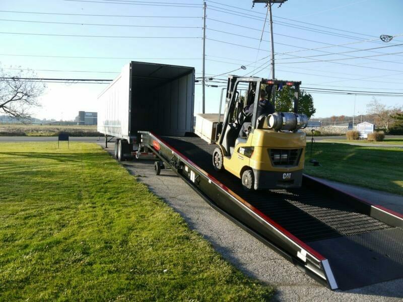 A forklift ascending a heavy duty loading ramp towards a tractor trailer | Heavy duty ramps