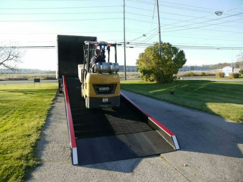 Yellow forklift accessing tractor trailer with a warehouse yard ramp