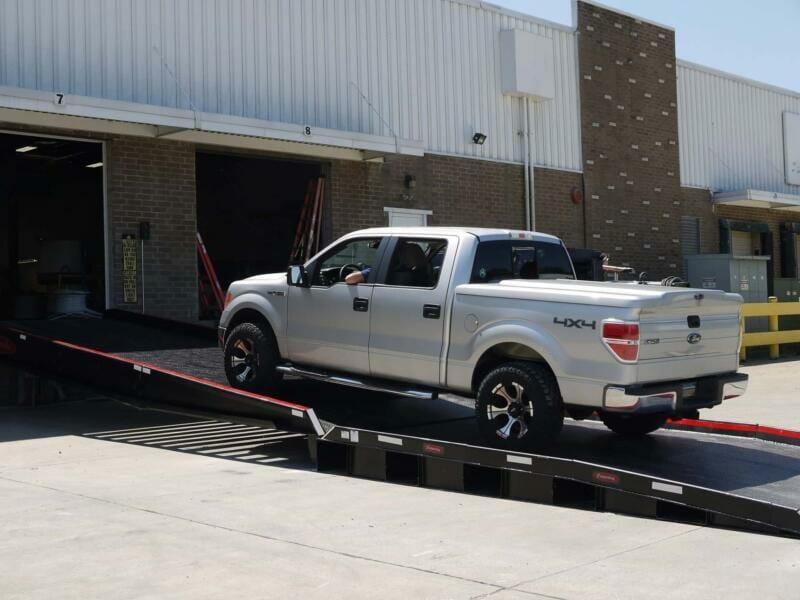 Pickup truck driving up warehouse dock ramp