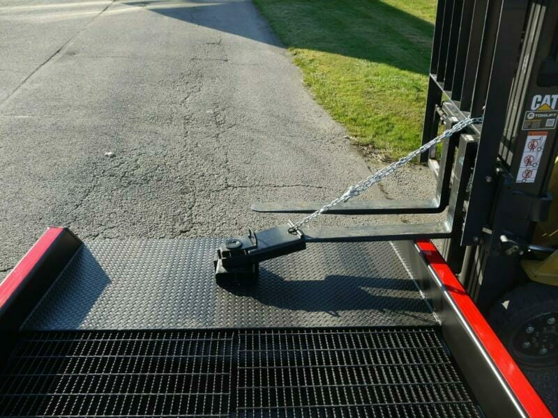 Semi truck ramp positioning sleeve with chain attached to forklift