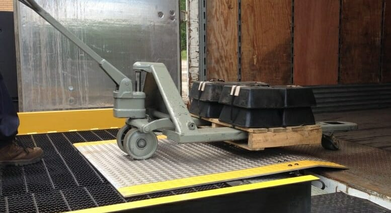 A hand cart moving a pallet over a Copperloy dock plate