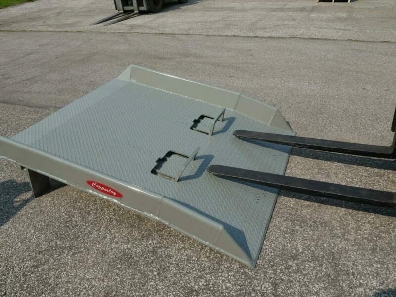 Forklift forks preparing to lift Copperloy steel dock board
