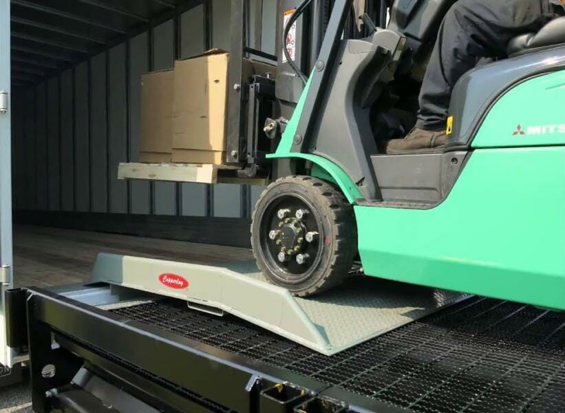Green forklift carrying pallets over a Copperloy dock board