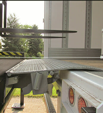 Hydraulic edge of dock leveler lying flat on truck bed as forklift prepares to travel over it.