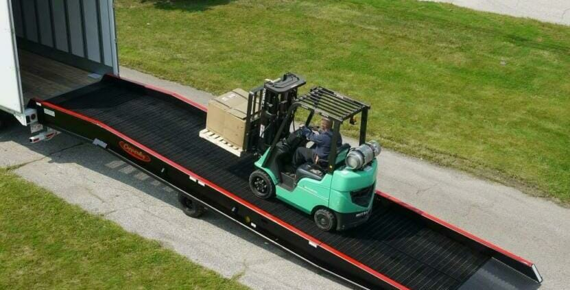 Green forklift carrying pallet towards semi truck on a heavy duty truck ramp | Heavy duty truck ramps by Copperloy